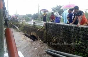 Petugas juru pengairan saat berupaya mengangkat sampah bambu yang menyumbat di bawah jembatan. (Dok Dinas PU Pengairan Banyuwangi)
