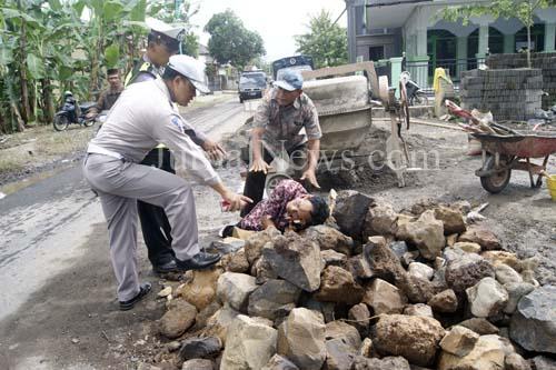 Olah TKP-Petugas dari unit Lalu Lintas Polsek Gambiran saat olah TKP. Dilokasi kejadian banyak material proyek menutupi separuh jalan. (Ron/Jn)