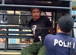 Berdarah-Pelaku pencurian, Husen, saat dievakuasi polisi dengan mobil patroli. (Ron/JN)