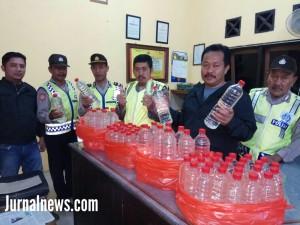 Foto: Kanit Reskrim Ipda Haryanto.sh saat menunjukkan minuman keras arak siap edar. ( Dok.Polsek Cluring).