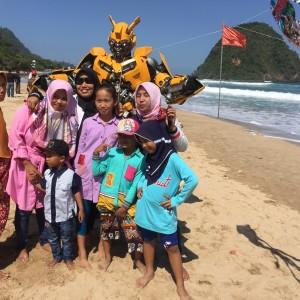Foto: Pengunjung foto bersama robot Bumblebee dipantai wisata pulau merah
